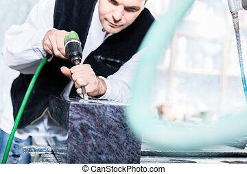 Stonemason working with pneumatic chisel