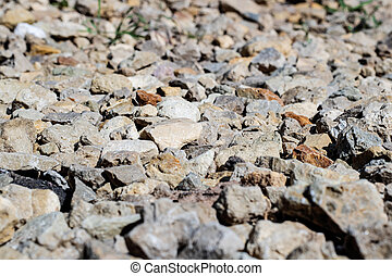 Stones and a piece of asphalt on a footpath close-up