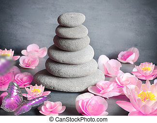stones balance with flower lily and butterfly on grey background