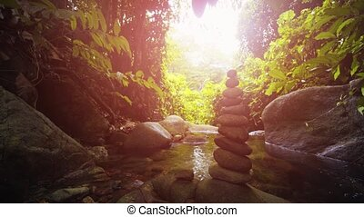 Stones balanced carefully into a vertical cairn, standing beside a peaceful, mountain stream