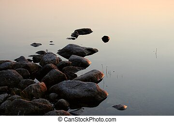 Stones in calm sunset water