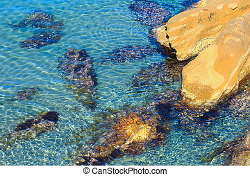 Stones in clear sea water.