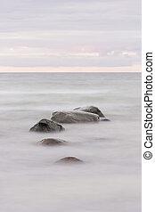 Stones in ocean at sunset