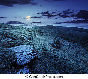 stones in valley on top of mountain range at night -...