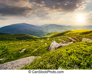 stones in valley on top of mountain range at sunset -...
