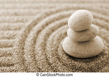 Macro of three staked stones on raked sand