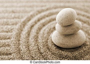 Macro of three staked stones on raked sand