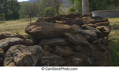 Stones made into a low fence - A hand held fade in shot of...
