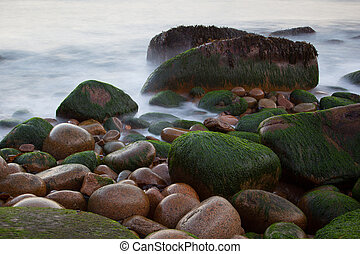 Stones on Otter cliffs coast with blurred water, Acadia...