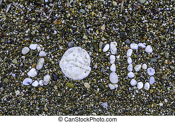 Stones on sand closeup. New Year. 2016. Beach. Copy space