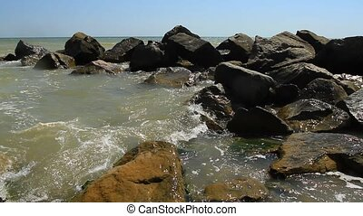 Stones on the black sea with waves