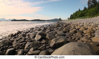Stones on the coast of Pacific Ocean on background amazing landscapes in Alaska.