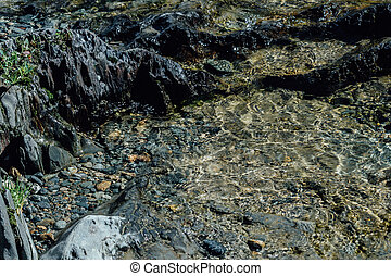 Stones, pebbles and sand on the shore of a mountain river