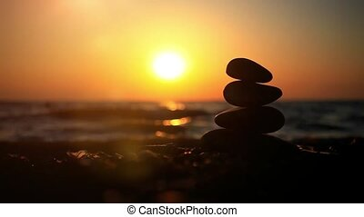 Stones pyramid on beach symbolizing zen, harmony, balance. Sea at sunset in the background. Changes focus to blurred. HD. 1920x1080