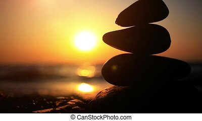 Stones pyramid on beach symbolizing zen, harmony, balance. Sea at sunset in the background. Changes focus to blurred and splashing waves