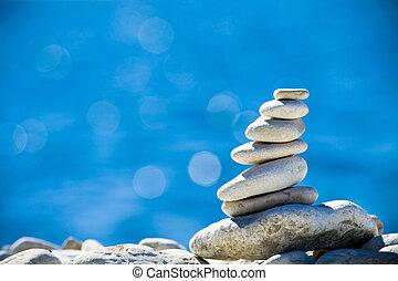 Stones stack over blue sea