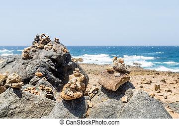 Stones Stacked on Black Volcanic Rock