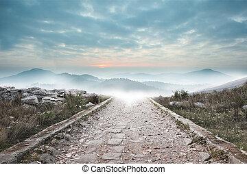 Stony path leading to misty mountain range