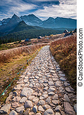 Stony path to the mountains valley at sunset in autumn