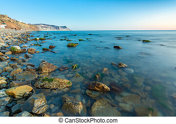 Stony sea beach of the 40th anniversary of the victory of the high coast of Anapa at sunset, Black Sea, Anapa, Russia