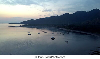 Stony seacoast and mountains on a sunset. Indonesia....