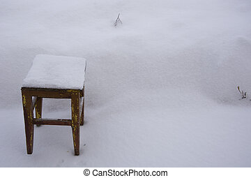 Stool in a snowdrift. Old wooden chair in the snow. There is a lot of snow in the garden in winter.