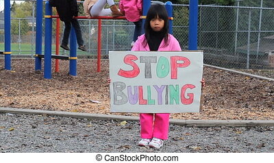 Stop Bullying Message - A little Asian girl carries a home...