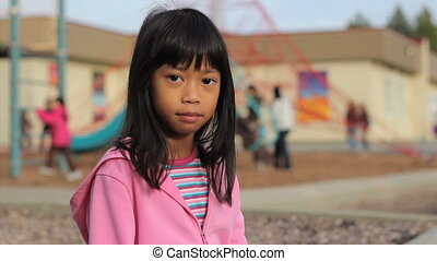 Stop Bullying Now Message - A cute little Asian girl holds...