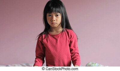 "A sad 6 year old Asian girl holds a ""stop bullying"" sign."