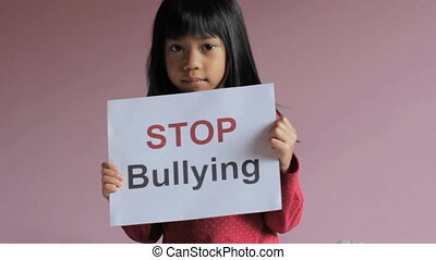 Stop Bullying Sign - A sad 6 year old Asian girl holds a...