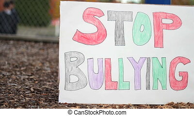 Stop Bullying Sign At School - Students play basketball in...