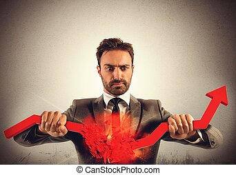 Stop financial trends - Angry businessman breaks a big red...