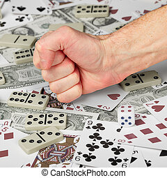 The hand clenched in a fist against the background of cards and money.