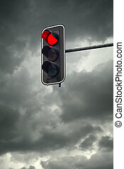 Stop light, the red traffic light on a cloudy day