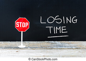 STOP LOSING TIME message written on chalkboard
