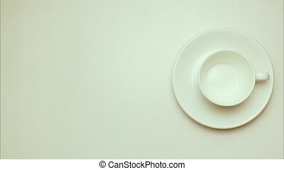 Stop motion, animation. Donut on a plate and a cup of coffee on a saucer. Top view