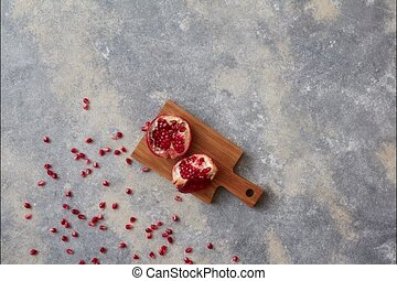Stop motion animation moving grains of pomegranate and two halves of ripe juicy fruit on a gray stone background appear and disappear.