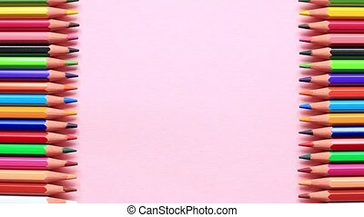 Stop motion animation of the movement of colored pencils on a pink background.