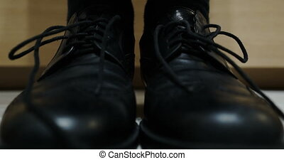 Stop motion animation - tying shoelaces on black shoes. -...