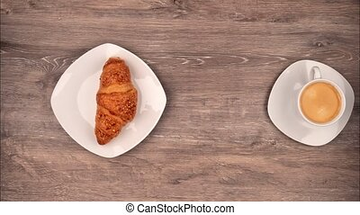 Stop motion from breakfast with a croissant and a coffee.