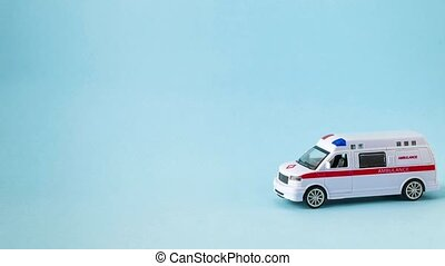 Stop motion. Toy ambulance rides on a blue background. High quality FullHD footage