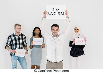 Stop racism, no racial discrimination of people. Young Caucasian man holds a poster with No racism text, while standing together with multiethnical friends with slogans on white background indoors