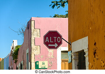 Stop sign on street corner with colorful colonial buildings in Campeche, Mexico