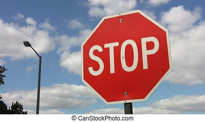 Stop sign with timelapse clouds.