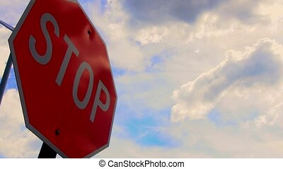 Stop sign with fast moving clouds
