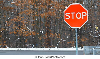 Stop sign with traffic cars in winter