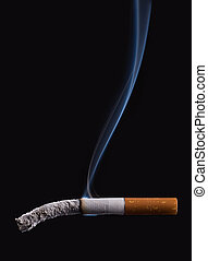 Stop smoking - Cigarette burning on dark black background...
