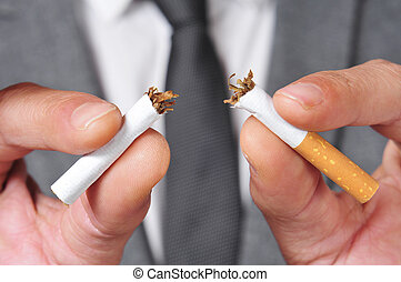 stop smoking - a man wearing a suit breaking a cigarette...