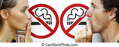 stop smoking - couple smoking a no smoking sign