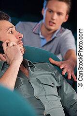 Stop talking! Young men talking at phone while watching movie at cinema